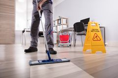 male-janitor-cleaning-floor-in-office-126317803